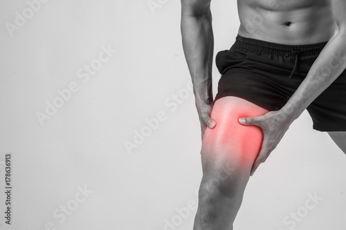 Fotografie, Tablou  Young sport man with strong athletic legs holding knee with his hands in pain after suffering ligament injury  isolated on white