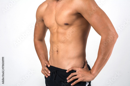 Fotomural  Muscular man showing six pack abs isolated on white background.