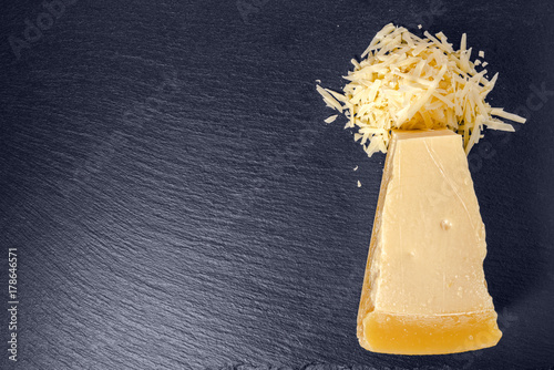 top view of tasty fresh yellow big segment piece hard parm and large grated cheese on stone slate background, close up