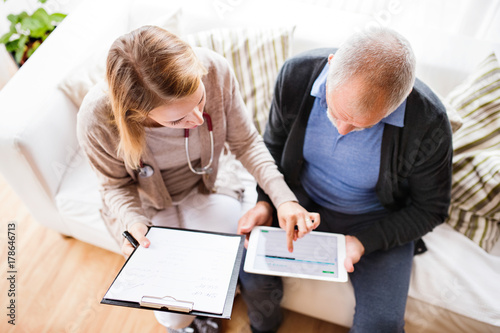 Obraz Health visitor and a senior man with tablet during home visit. - fototapety do salonu