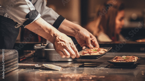 Fototapeta Hand of man take cooking of meat with vegetable grill, Chef cooking wagyu beef in Japanese teppanyaki restaurant obraz