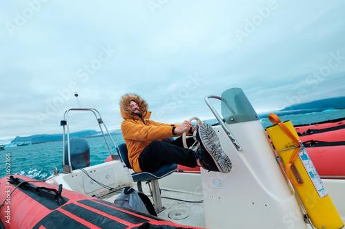 Deurstickers Poolcirkel Happy man on a boat on the icy lagoon of Joculsarlon, Iceland