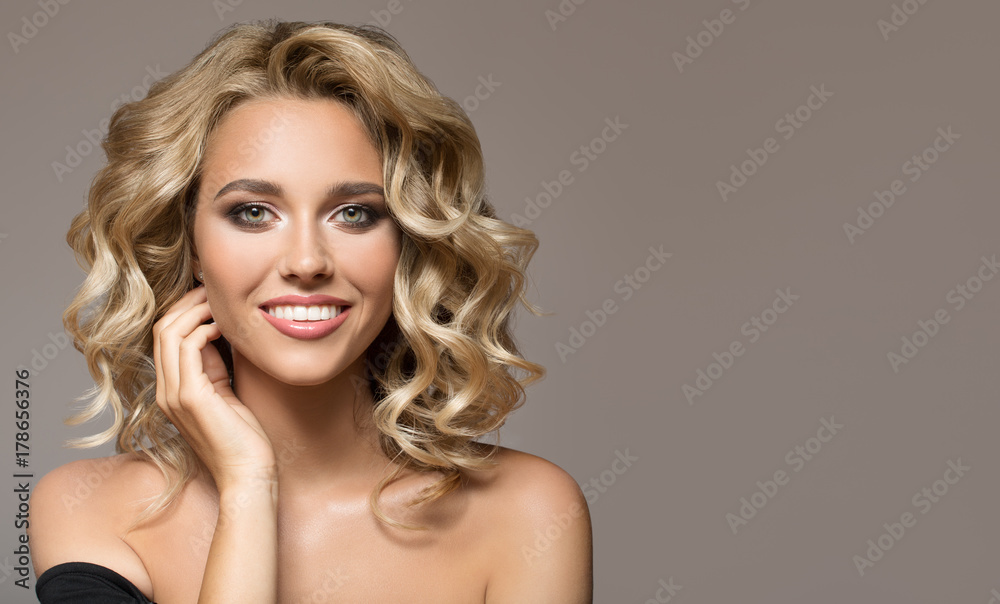 Fotografiet Blonde woman with curly beautiful hair smiling on gray background