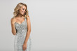 canvas print picture - Beautiful woman in shining silver dress on gray background.