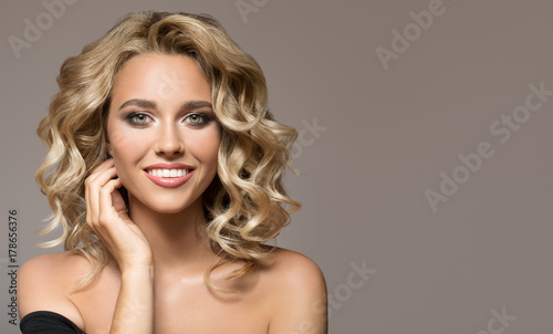 Foto  Blonde woman with curly beautiful hair smiling on gray background