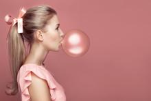Beautiful Blonde Woman Blowing Gum. Fashion Portrait On Pink Background.