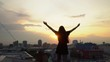 The beautiful young girl jumps with the raised hands and smiles against the background of the evening city. the girl on a roof of the multystoried building. Silhouette of a young happy girl feeling