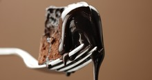 Closeup Of Piece Of Chocolate Cake On A Fork With A Liquid Topping