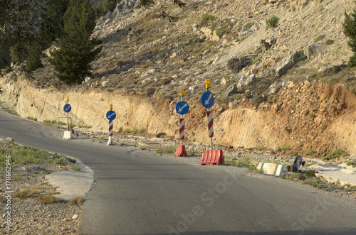 Fotografie, Obraz  Road signs direction of movement at the foot of the mountain, with rockfalls on