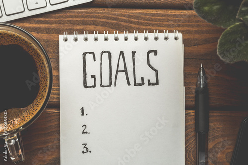 Photo  Top view of notepad with Goals List, cup of coffee on wooden table, goals concep