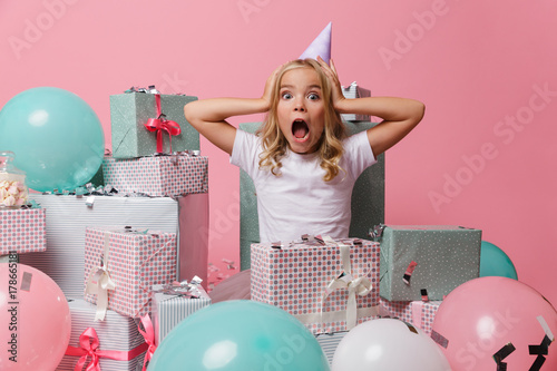 Fototapeta Portrait of a pretty little girl in a birthday hat obraz
