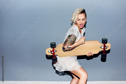 Photo  Tattooed pretty blond girl goofing around, playing longboard as guitar and singi