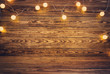 canvas print picture Old wooden planks with christmas decoration. Brown background with lightbulbs