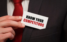Businessman Putting A Card With Text KNOW YOUR COMPETITORS In The Pocket