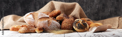 Photo Stands Bread Assortment of baked bread and bread rolls on wooden table background.