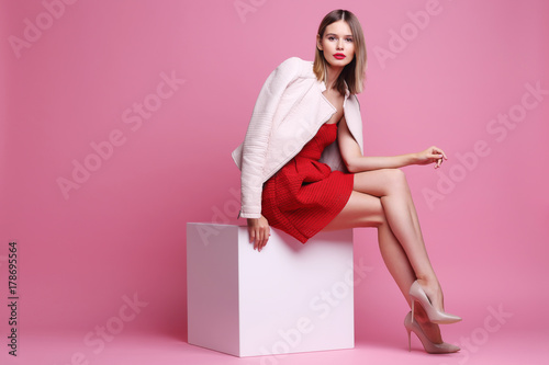 Fotomural Fashion portrait of young woman in pink leather jacket and red dress