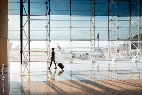 View on the aiport window with woman walking with suitcase at the departure hall of the airport Fototapeta