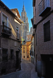 Fototapeta Uliczki - Narrow street opening to a high cathedral