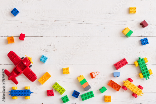 Fotografia, Obraz Top view on multi-color toy bricks on white wooden background