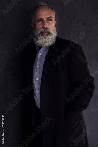 Foto op Aluminium Aap Pensive bearded man looking somewhere while posing in dark studio