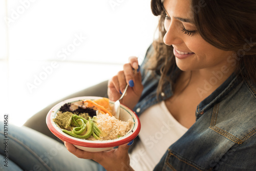 Deurstickers Kruidenierswinkel Woman eating a vegan bowl