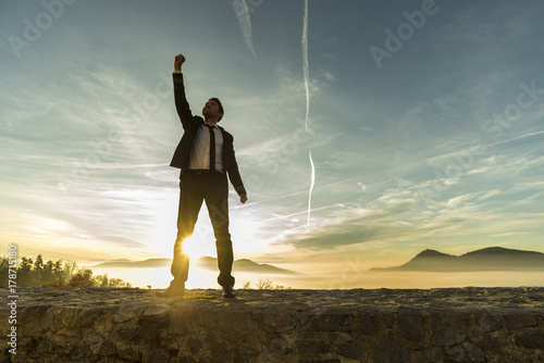 Triumphant businessman greeting a new day Fototapeta