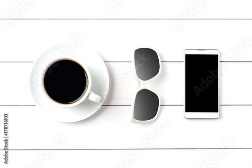 Zdjęcie XXL Filiżanka, okulary przeciwsłoneczni i mądrze telefon na białym drewnianym tle ,.
