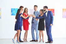 Group Of People In Formal Wear Drinking Champagne At Art Gallery Exhibition