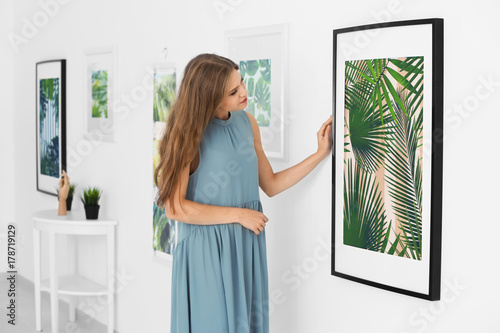 Fotografia, Obraz Young woman looking at picture of tropical foliage in art gallery