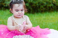 Baby Toddler Girl First Birthday Anniversary Party, Playing With Candle, Dirty Face And Making A Mess Of Pink Cake With Candle. Princess Costume