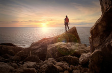 Sunset View. Man With Backpack. Rocks At The Sea Ocean Bank