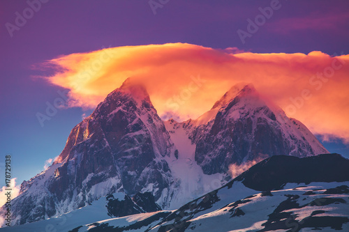 Foto op Aluminium Snoeien Colorful sunset over the snowy mountain peaks with dramatic overcast pink clouds sky. Travel nature background. Holiday, sport, recreation. Kazbegi National Park, Gergeti, Georgia. Retro toning filter