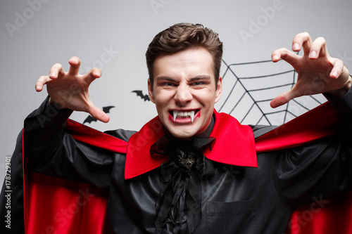 Vampire Halloween Concept - Portrait of handsome caucasian Vampire halloween costume fluttering his red, black cloak.