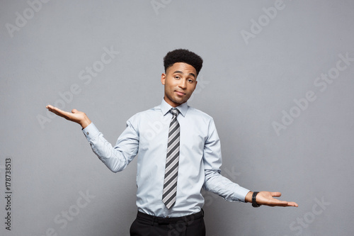 Deurstickers Ontspanning Business Concept - Confident thoughtful young African American showing balancing hands on side over grey background.