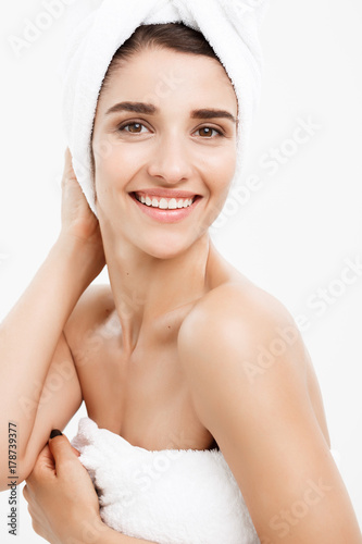 Fotografie, Obraz  Beauty & Skin care concept - Beautiful caucasian Young Woman with bath towel on head covering her breasts, on white touching her skin