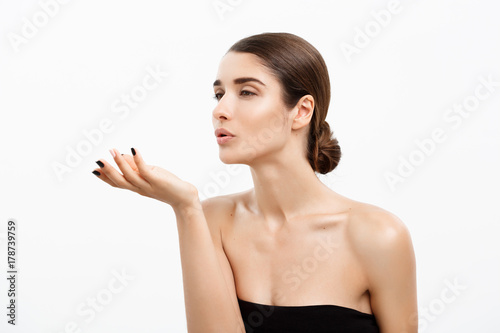 Photo Health care and spa concept - attractive young and healthy woman blowing a kiss from her hand white background