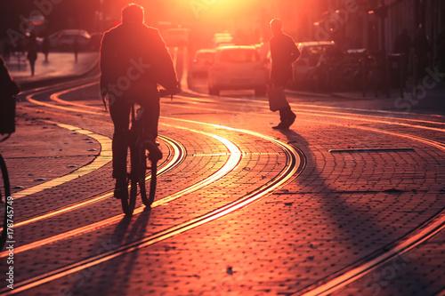 Fototapeta Zamazujący ludzie jedzie bicykl podczas zmierzchu w mieście Bordo w rocznika stylu i zbożowa tekstura z kopii przestrzenią