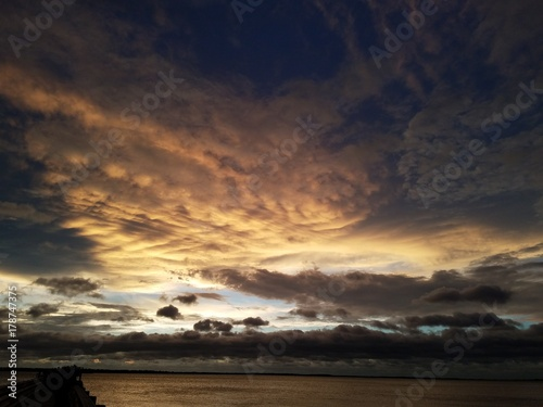 Spoed Foto op Canvas Zee zonsondergang Stormy cloudscape over the water at sunset