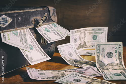 Retro suitcase full of money on the table, scattered dollar