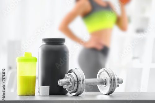 Composition with metal dumbbell, protein shake and blurred woman on background