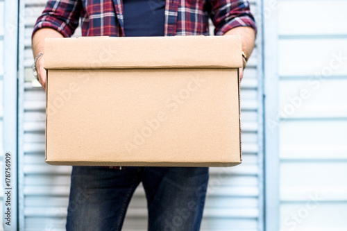 Fotografia Young man holding a moving cardboard box in front of a storage door