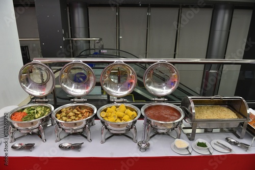 food, catering, self-service and eating concept - Buffet food serving on metallic tray. Prepare for wedding party. Metal buffet heated trays with food on tables at banquet event celebration