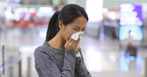 Fototapeta Woman sneezing the airport