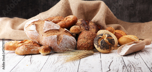 Assortment of baked bread and bread rolls on wooden table background.