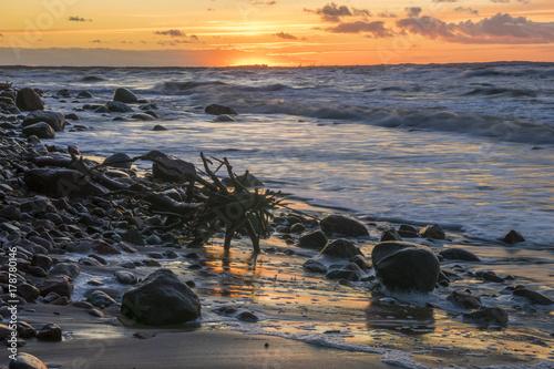 Plakat zachód słońca nad morzem podczas burzy, fale rozbijające się o kamienie