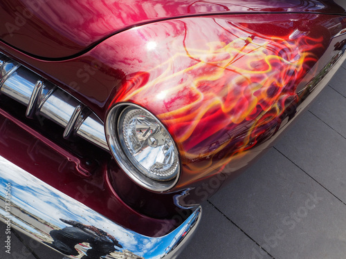 Canvas Print Classic American custom muscle car with flames painted behind headlight