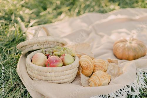 Plakat na polanie wiklinowy kosz z winogronami i jabłkami obok rogalików