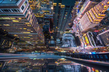 Fototapeta Bird's eye view of Manhattan, looking down at people and yellow taxi cabs going down 5th Avenue.