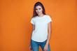 Leinwandbild Motiv Sexy woman in a white T-shirt on the orange background. Mock-up.