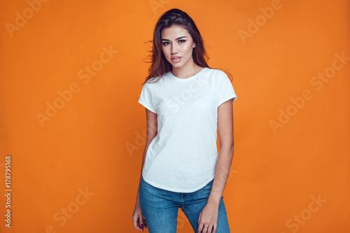 Obraz Sexy woman in a white T-shirt on the orange background. Mock-up. - fototapety do salonu